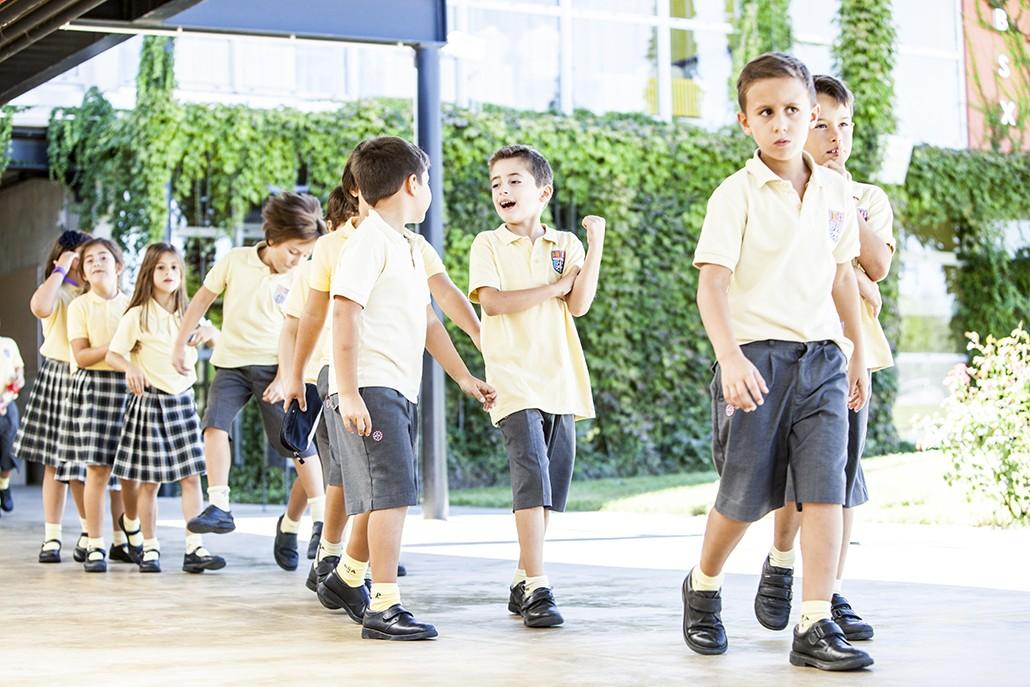 niños de primaria por los pasillos de british school