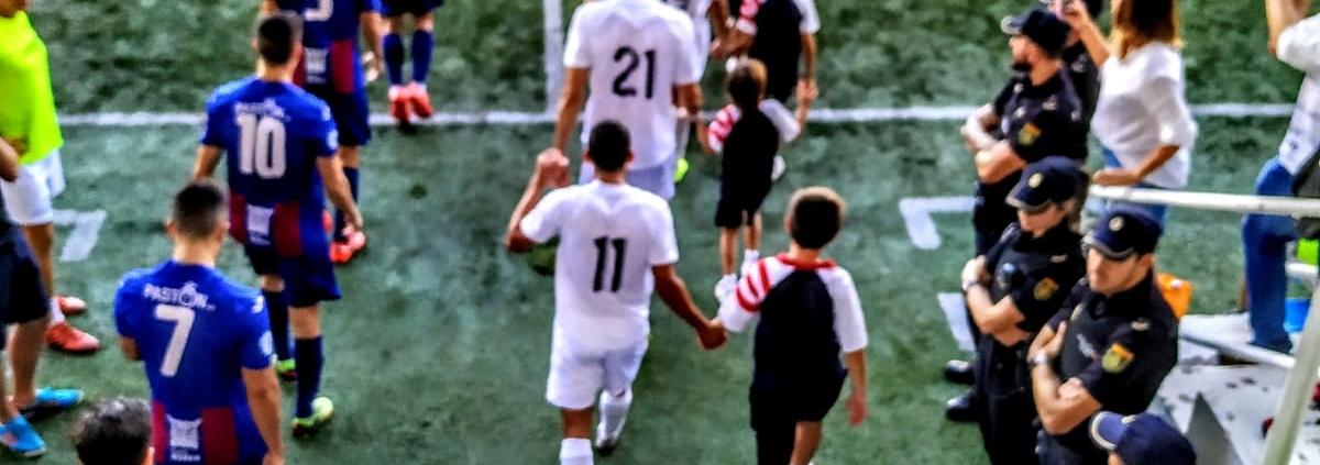 alumnos de BSX entrando al campo con los jugadores del CD Olímpic de Xàtiva